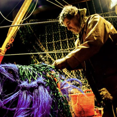 Fisherman mending nets at Newlyn Harbour (Photo by Laurence Hartwell)