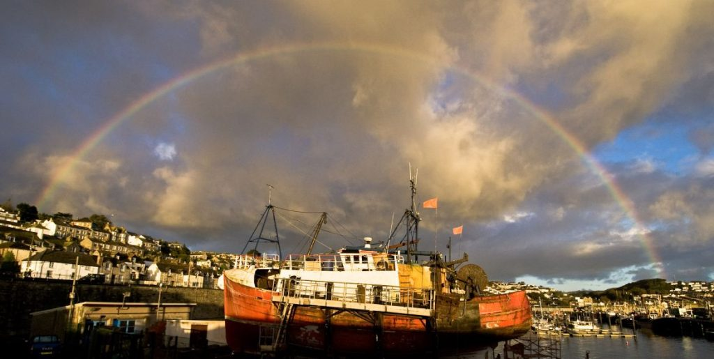 Fishing boat on Newlyn Harbour repair cradle with rainbow above spanning across the whole harbour (photo by Laurence Hartwell)