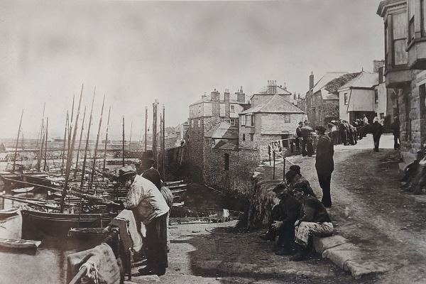 Historic photo of Old Quay Newlyn, with sailing fishing boats and fishermen and nets drying