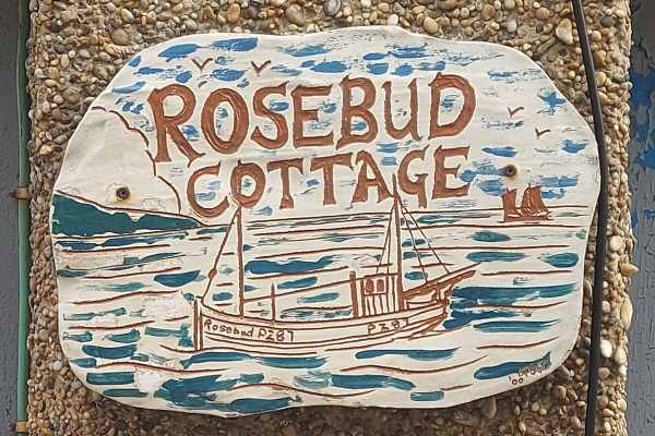 Rosebud Cottage house plaque with a drawing of the Rosebud PZ87 fishing boat on the sea